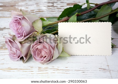 Purple roses bouquet and blank greeting card over wooden table. Top view with copy space - stock photo