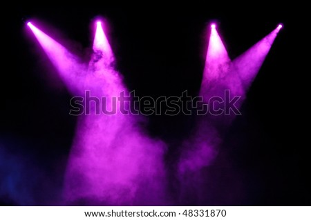 Purple stage spotlights in smoke over black background - stock photo