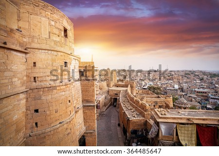 Purple sunset at sandstone desert city with Jaisalmer fort in Rajasthan, India - stock photo