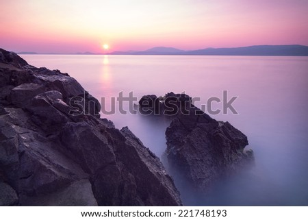 Purple sunset over sea, majestic rocks in the fog, beautiful beach landscape, wonderful panoramic scene in Europe, travel and tourism concept - stock photo
