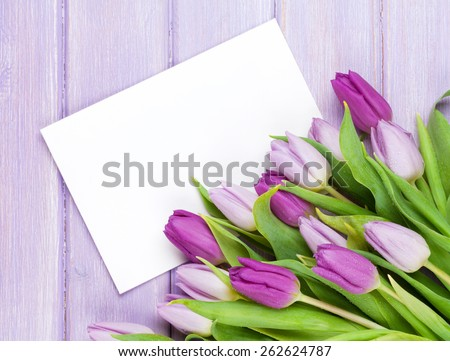 Purple tulip bouquet and blank greeting card. Top view over wooden table - stock photo