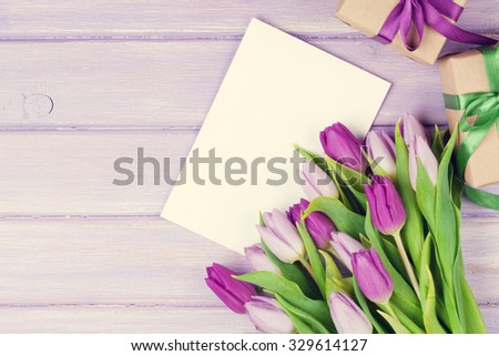 Purple tulip bouquet, blank greeting card and gift boxes. Top view over wooden table. Toned - stock photo