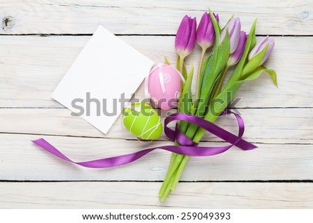 Purple tulip bouquet, easter eggs and blank greeting card. Top view over white wooden table - stock photo