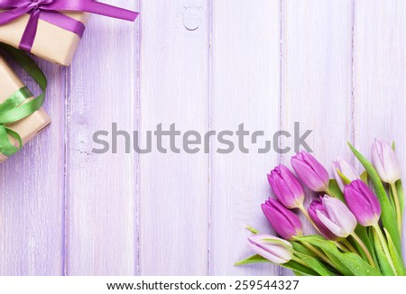 Purple tulips and gift boxes over wooden table. Top view with copy space - stock photo