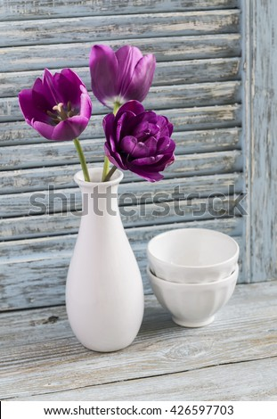 Purple tulips in a ceramic vase and white ceramic bowl on a blue wooden background. Still life in vintage and rustic style - stock photo