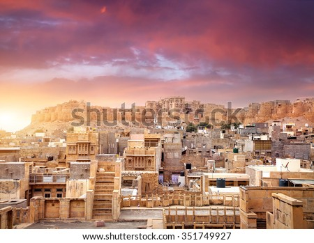 Purple vibrant sunset at indian desert city with Jaisalmer fort in Rajasthan, India - stock photo