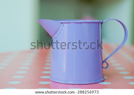 purple watering pot on the table - stock photo