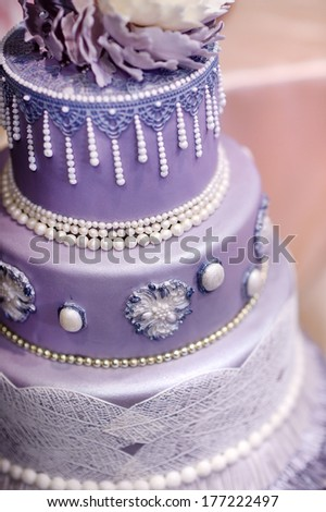 Purple wedding cake decorated with flowers and pearls - stock photo