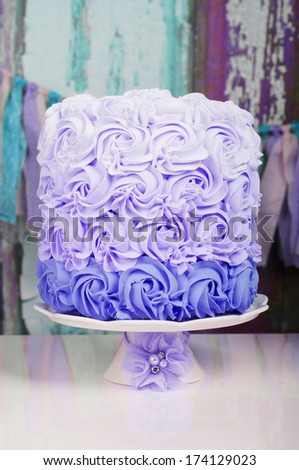 purple wedding cake on a cake stand with flower decoration - stock photo