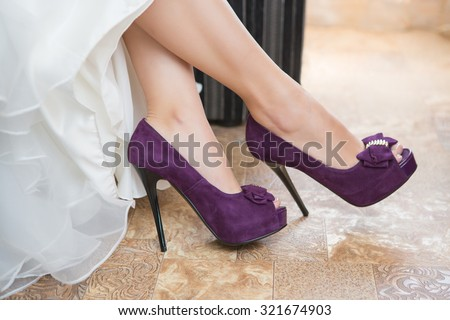 Purple Wedding shoes on the feet of the bride - stock photo