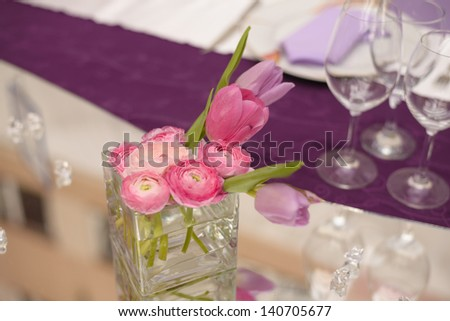 Purple wedding table decoration with pink flower - stock photo