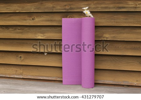 purple Yoga mat and flower beside old wooden wall  background - stock photo