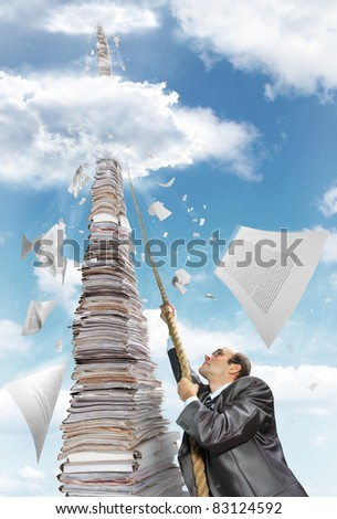 Purposeful businessman climbing up the pile of paperwork - stock photo