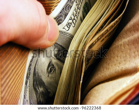 Purse in arm with the big pack of dollars - stock photo