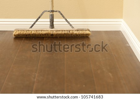 Push Broom on a Newly Installed Laminate Floor and New Baseboards. - stock photo