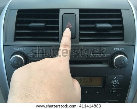 Push emergency button in car, hazard light - stock photo