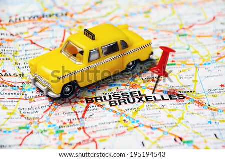 push pin pointing at Brussels, Belgium and  a taxi  - stock photo