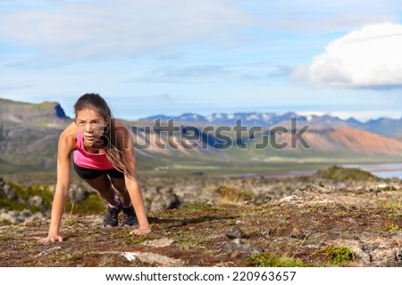Push-ups fitness woman doing pushups or plank outside in amazing nature landscape on Iceland. Fit female sport model girl training crossfit outdoors. Mixed race Asian Caucasian athlete in her 20s. - stock photo