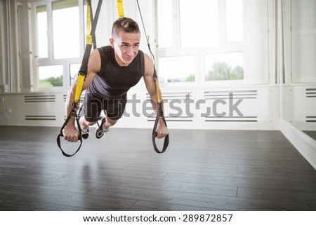 Push-ups on a suspension - stock photo