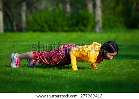 Push ups or press ups exercise by young woman. Girl working out on grass crossfit strength training in the glow of the morning sun - stock photo