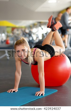 Push your way. Vertical shot of a young sporty woman training using fitness ball at the gym looking to the camera. - stock photo