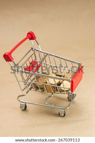 Pushcart with coins. Concept of shopping, on brown background - stock photo