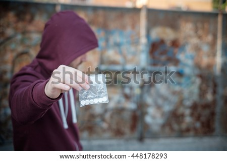 Pusher selling and trafficking drug dose - stock photo