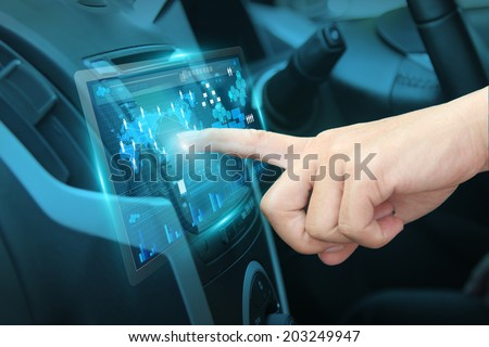 Pushing on car screen interface, With driver entering an address into the navigation system - stock photo