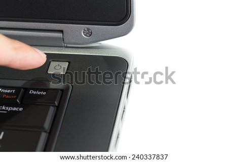 Pushing the Power Button on Laptop Computer on white background - stock photo