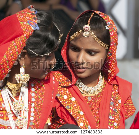 PUSHKAR, INDIA - NOVEMBER 21:  A pair unidentified girls in colorful ethnic attire attends at the Pushkar fair on November 21, 2012 in Pushkar, Rajasthan, India. - stock photo