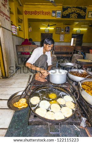 PUSHKAR, INDIA - OCTOBER 20: Local man prepares bakery in a pan on November 20,2012 in Pushkar, india. Pan cooking in India is common and mainly propane gas is used as heating material. - stock photo