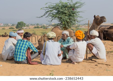 PUSHKAR, INDIA - OCTOBER 27, 2014: Unidentified Indian men attended the annual Pushkar Camel Mela. This fair is the largest camel trading fair in the world. - stock photo