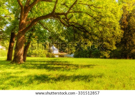 Pushkin, Saint Petersburg/Russia - August 11, 2015: View of park in Pushkin in summer day ('Grotto' Pavilion behind lawn and trees) - stock photo