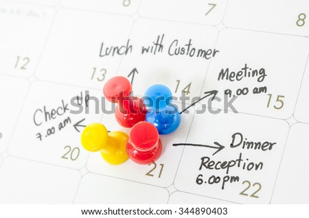 Pushpin on calendar with busy day overworked schedule. - stock photo