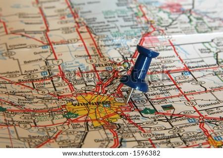 pushpin stuck on a map - stock photo
