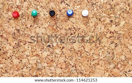 Pushpins  on a cork board. - stock photo
