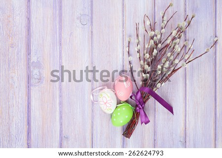 Pussy willow and easter eggs over wooden table background with copy space - stock photo