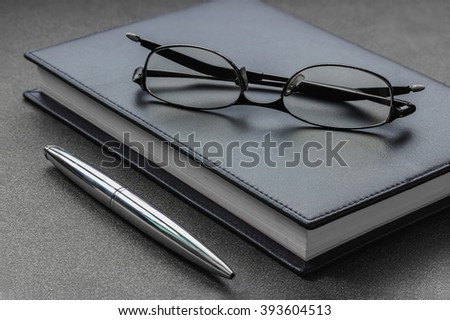 Put the glasses and pen on a notebook, rest one's eyes. - stock photo