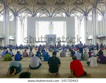 PUTRAJAYA - JULY 13: Muslim performing Friday prayers at Tuanku Mizan Mosque  on July 13, 2013 in Putrajaya Malaysia. Friday prayer is perform just after noon in the place of dhuhr - stock photo
