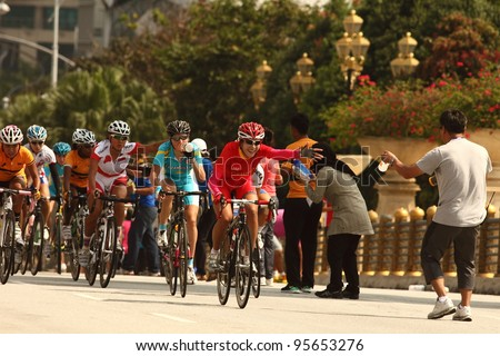 PUTRAJAYA, MALAYSIA - FEB 17:  Female cyclists enter an uphill feed zone in 120km Road Race Woman Elite during the 32nd Asian & 19th Junior Asian Cycling Championships on Feb 17, 2012 in Putrajaya, Malaysia - stock photo