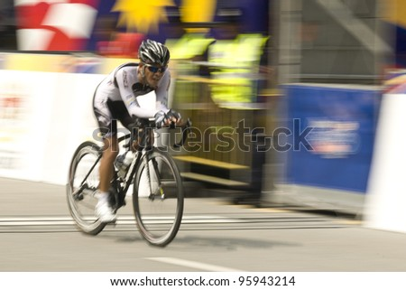 PUTRAJAYA, MALAYSIA - FEBRUARY 24: An unidentified cyclists participates in Stage 1 of the  Putrajaya Individual Time Trial for the 2012 Le Tour de Langkawi on Feb. 24, 2012 in Putrajaya, Malaysia - stock photo