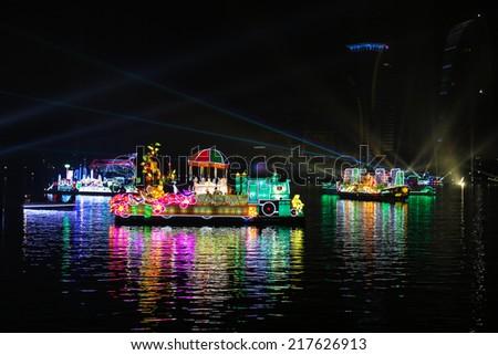 PUTRAJAYA, MALAYSIA- JUNE 21, 2014 : Sabah floats cruising at lake during FLORIA night show in Putrajaya, Malaysia, showcasing their unique tourism attraction. - stock photo