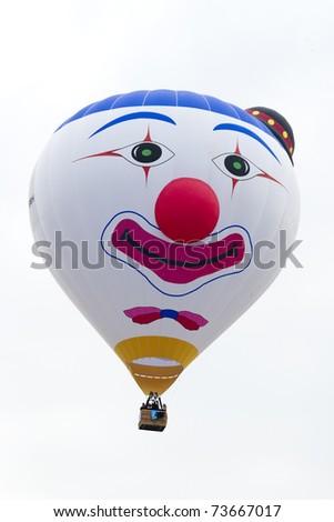 PUTRAJAYA, MALAYSIA-MAR 19:Clown face balloon from Belgium in flight at 3rd Putrajaya International Hot Air Balloon Fiesta Mar 19, 2011 in Putrajaya.More than 300,000 people visit this yearly event - stock photo