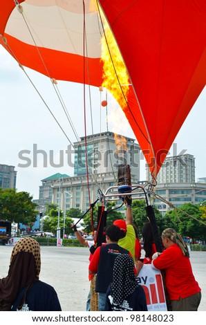 PUTRAJAYA, MALAYSIA-MAR 17: Crew members open up the flame into the balloon at the 4th Putrajaya International Hot Air Balloon Fiesta Mar 17, 2012 Putrajaya, Malaysia. - stock photo