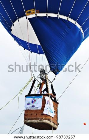 PUTRAJAYA, MALAYSIA-MAR 23:Tethered hot air balloon provides rides for visitor at the 3rd Putrajaya International Hot Air Balloon Fiesta March 23, 2011 in Putrajaya. Malaysia. More than 300,000 people visit this year event - stock photo