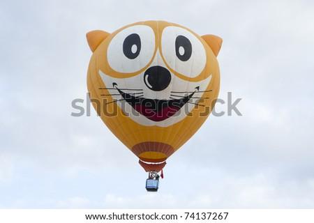 PUTRAJAYA, MALAYSIA-MAR 19:Unique Cat face balloon in flight at the 3rd Putrajaya International Hot Air Balloon Fiesta Mar 19, 2011 in Putrajaya.7 special shape balloon participate in this year event - stock photo