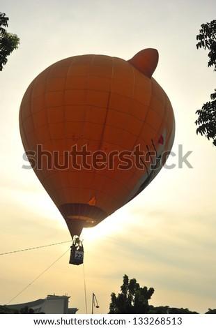 PUTRAJAYA, MALAYSIA - MARCH 29: A tethered hot air balloon flies over the horizon during 5th Putrajaya International Hot Air Balloon Fiesta at Presint 2, Putrajaya on March 29, 2013. - stock photo