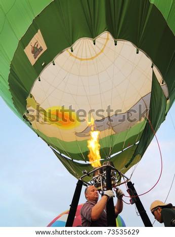 PUTRAJAYA, MALAYSIA - MARCH 19: Crew blast the burner flame into the Germany balloon envelope mouth during 3rd Putrajaya International Hot Air Balloon Fiesta on March 20, 2011 at Putrajaya, Malaysia. - stock photo