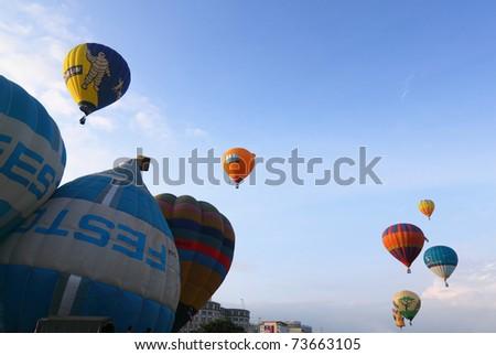 PUTRAJAYA, MALAYSIA - MARCH 19: Hot air balloons in various designs dot the sky over Putrajaya during 3rd Putrajaya International Hot Air Balloon Fiesta on 19 March, 2011 in Putrajaya, Malaysia. - stock photo