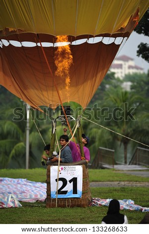 PUTRAJAYA, MALAYSIA - MARCH 29:Two passengers ascend up on the tethered hot air balloon during 5th Putrajaya International Hot Air Balloon Fiesta at Presint 2, Putrajaya on March 29, 2013. - stock photo